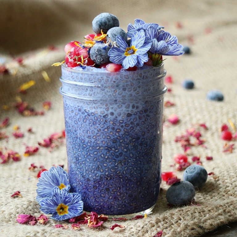 Layered Blue Chia Pudding with Butterfly Pea Flower Tea, topped with pomegranate sees, blueberries and edible flowers. Recipe on breakfastwithflowers.com