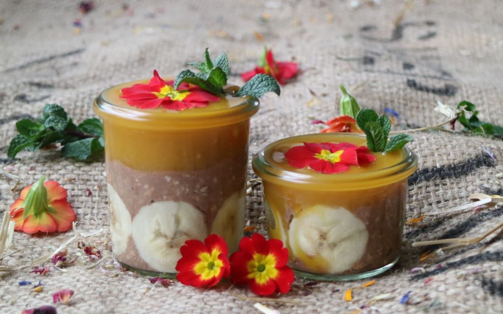 Coconut Infused Overnight Oats with Cacao and Mangopuree, decorated with edible flowers. More recipes on breakfastwithflowers.com