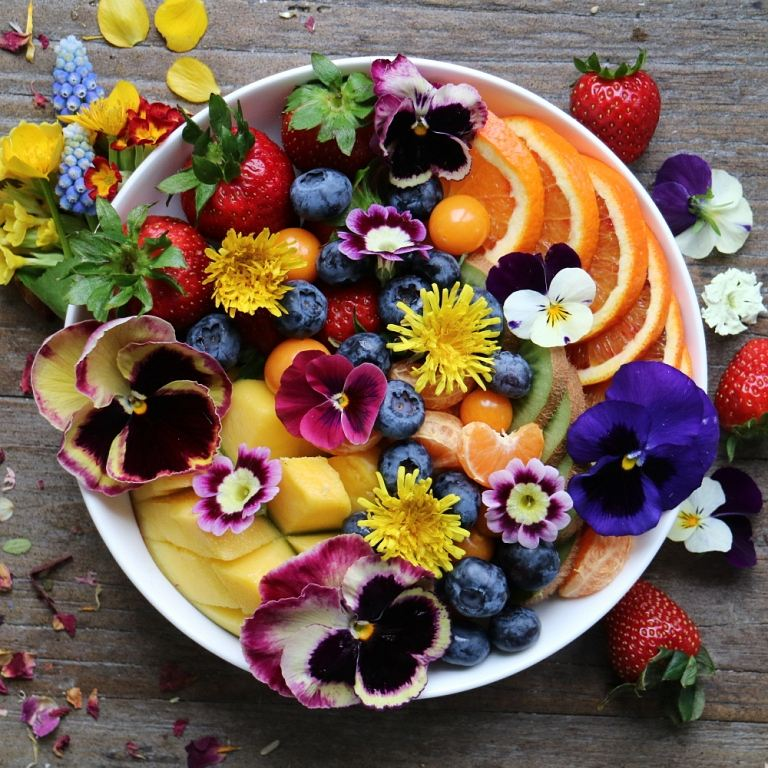 Fruit plate with edible flowers. More information about how to use edible flowers on breakfastwithflowers.com