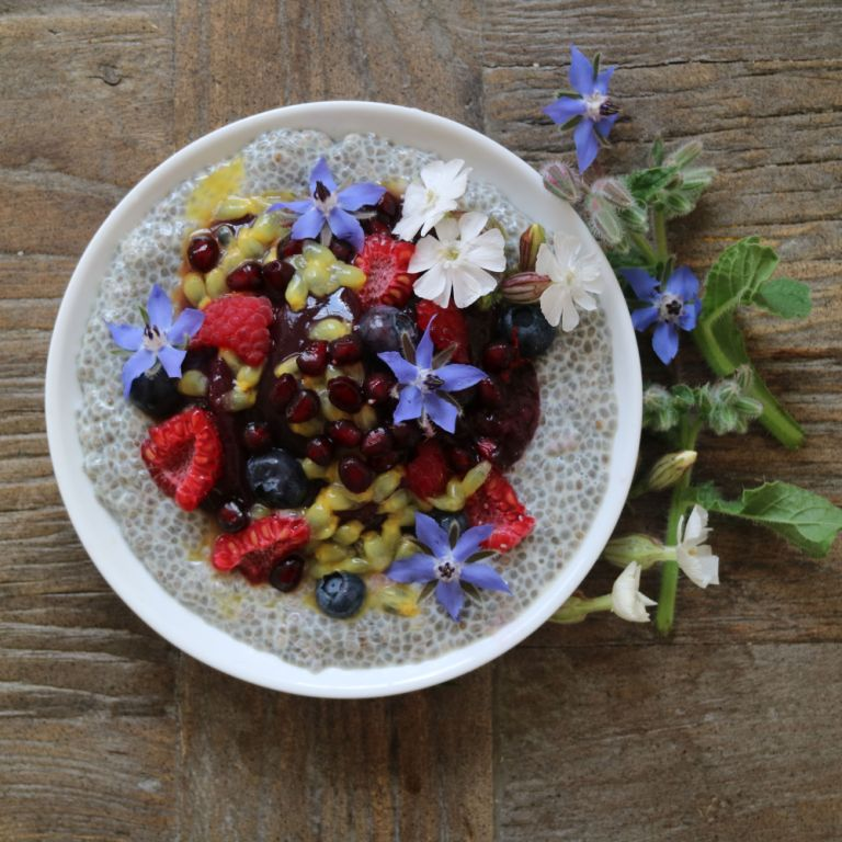 Chia Pudding topped with fruits and edible flowers. More recipes on breakfastwithflowers.com
