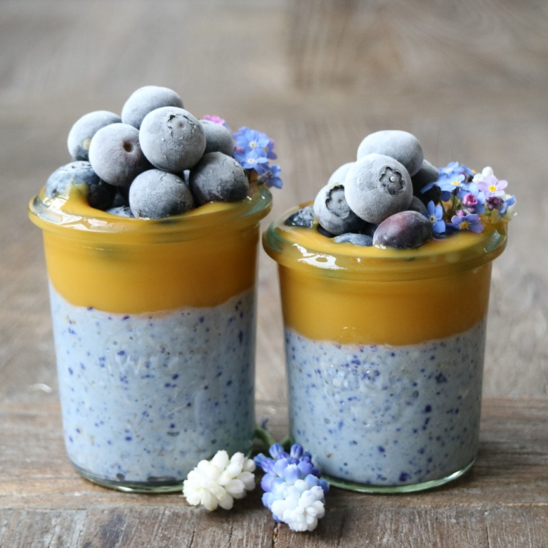Blue Overnight Oats with Butterfly Pea Flower Tea, topped with mango puree. Dairyfree, vegan, kidsfriendly. Recipe on breakfastwithflowers.com.