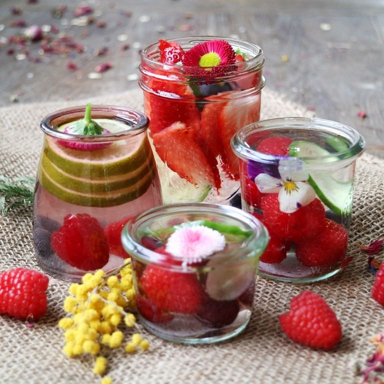 Infused water with strawberries, raspberries, lime and edible flowers. More information about how to use edible flowers on breakfastwithflowers.com