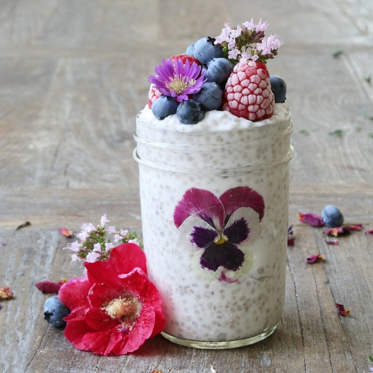 Gluten-free and vegan coconut chia parfait with blueberries and edible flowers. Full recipe on www.breakfastwithflowers.com/coconut-chia-parfait/