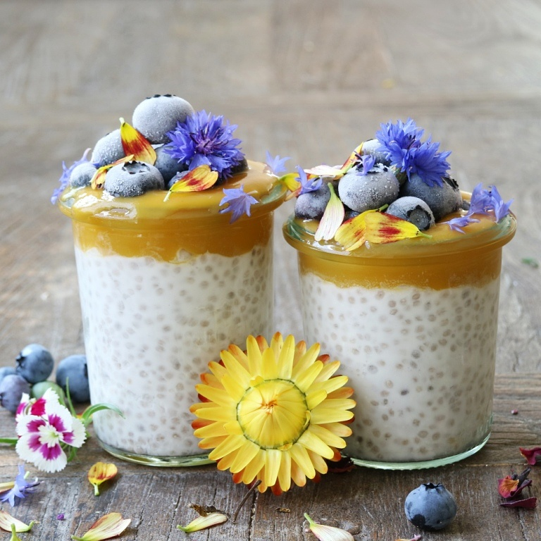 Vegan and gluten-free Coconut Chia Parfait topped with mango puree, blueberries and edible flowers. Full recipe on www.breakfastwithflowers.com/coconut-chia-parfait/