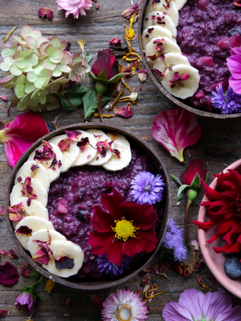 Blueberry Porridge with Vanilla bean and apple, decorated with edible flowers.