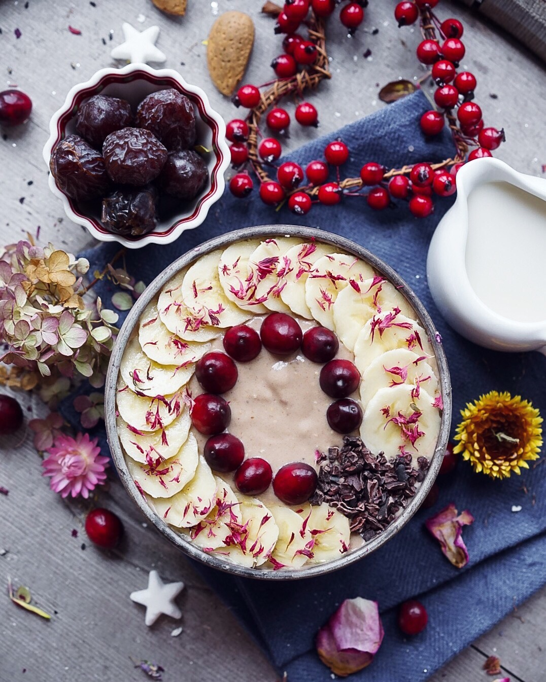 Salted Caramel Smoothie with Almonds, gluten-free and vegan. Toppings include banana slices, cranberries and dried flowers.